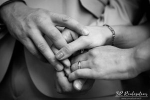 Photo de mariage en gros plan sur les mains des mariés entrelassées, noir et blanc